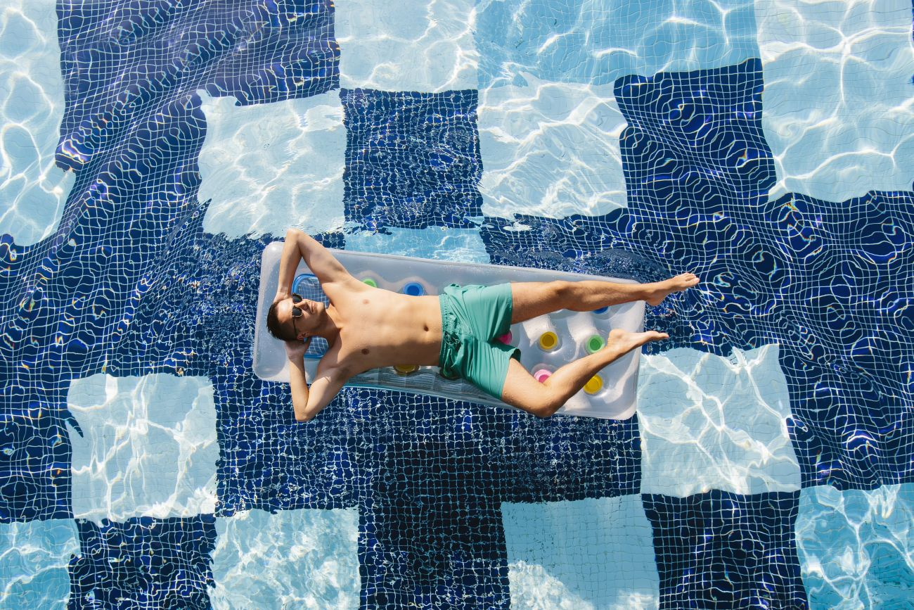 Man Floating in Pool on Vacation