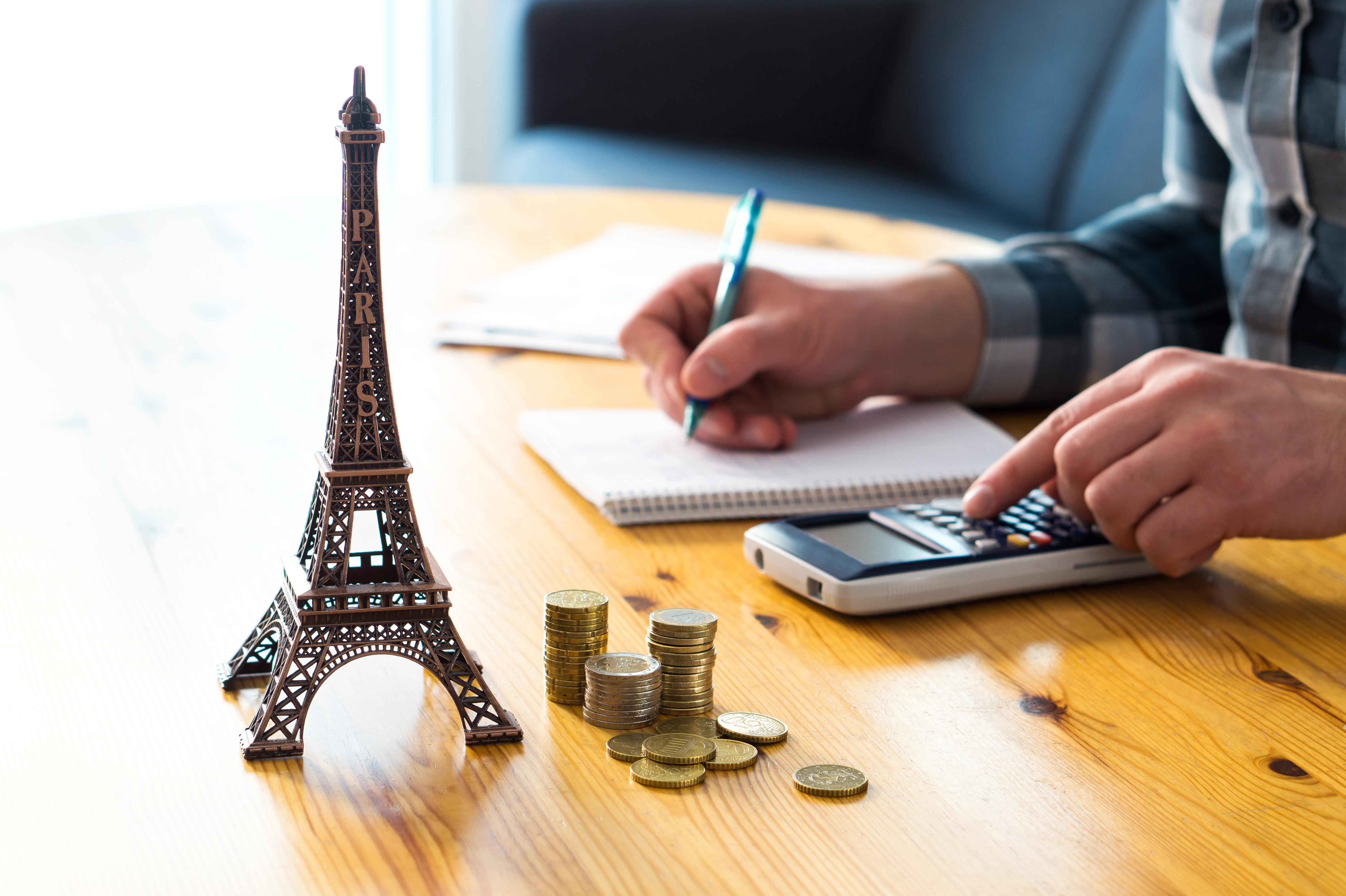Eiffel Tower and Coins on Travel Agents Desk