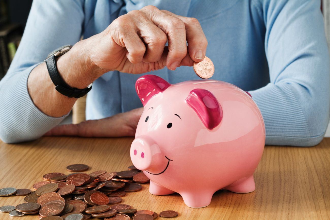 Retired Woman Putting Money in Piggy Bank