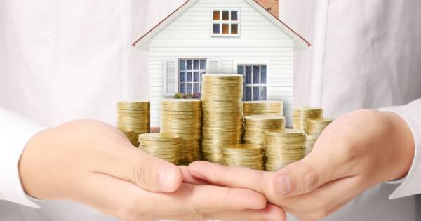 Woman Holding Little House and Gold Coin Stacks