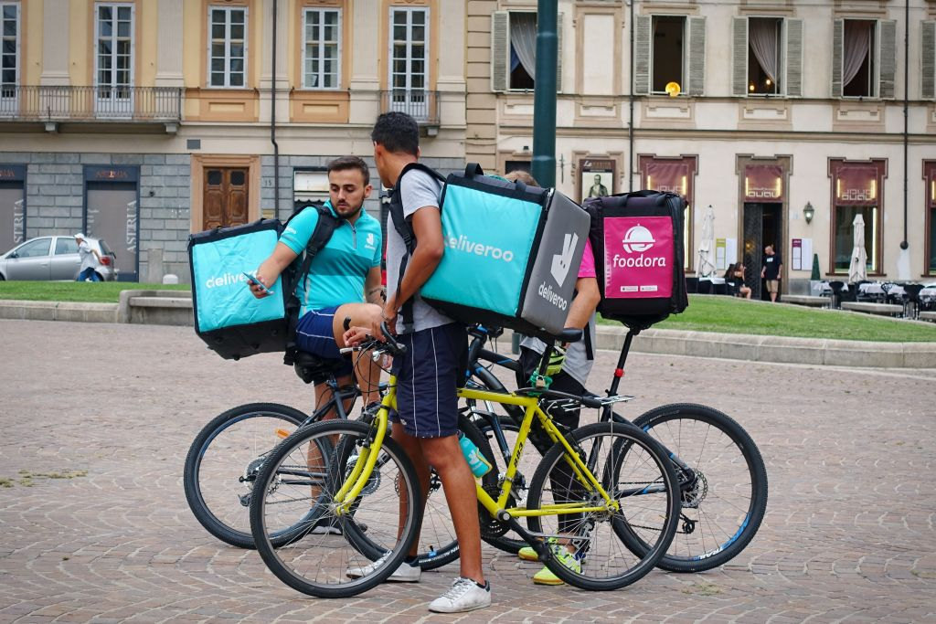 Gig Workers Looking at Phone on Delivery Bike