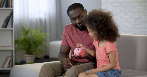 Child Putting Money into Piggy Bank Father is Holding
