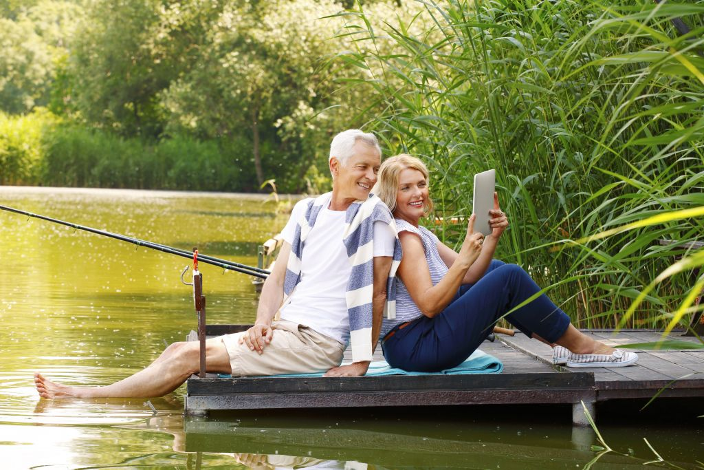 Retired Couple Relaxing on Dock with Tablet