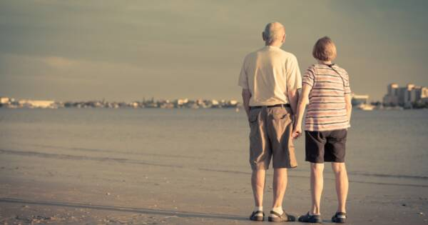 Retired Senior Couple Holding Hands at the Beach