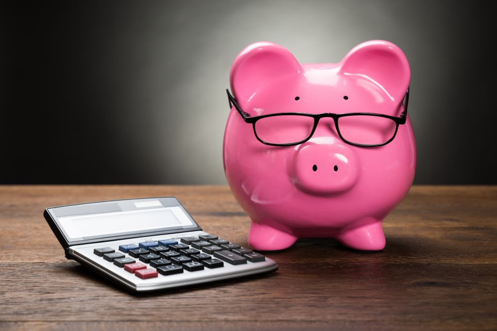 Piggy Bank and Calculator on Table