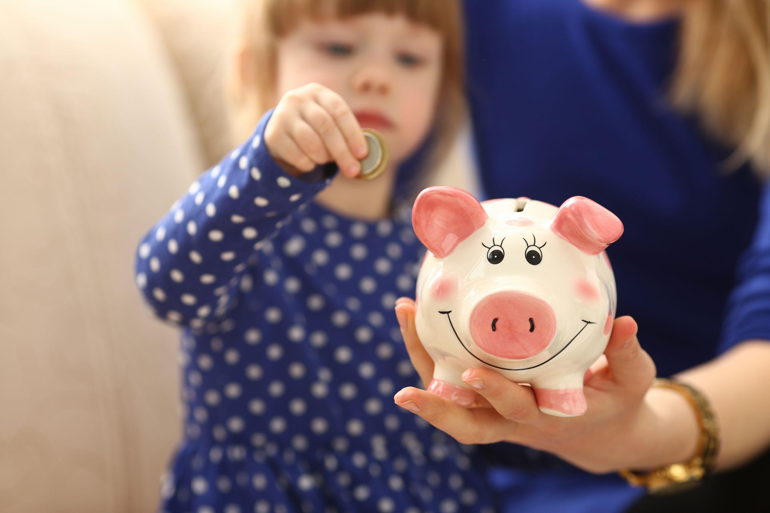 Kid Putting Money in Piggy Bank