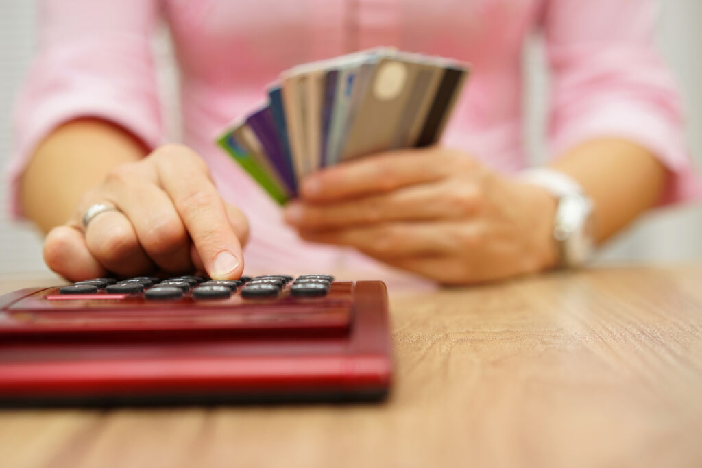 Woman Typing on Calculator with Credit Cards in Hand