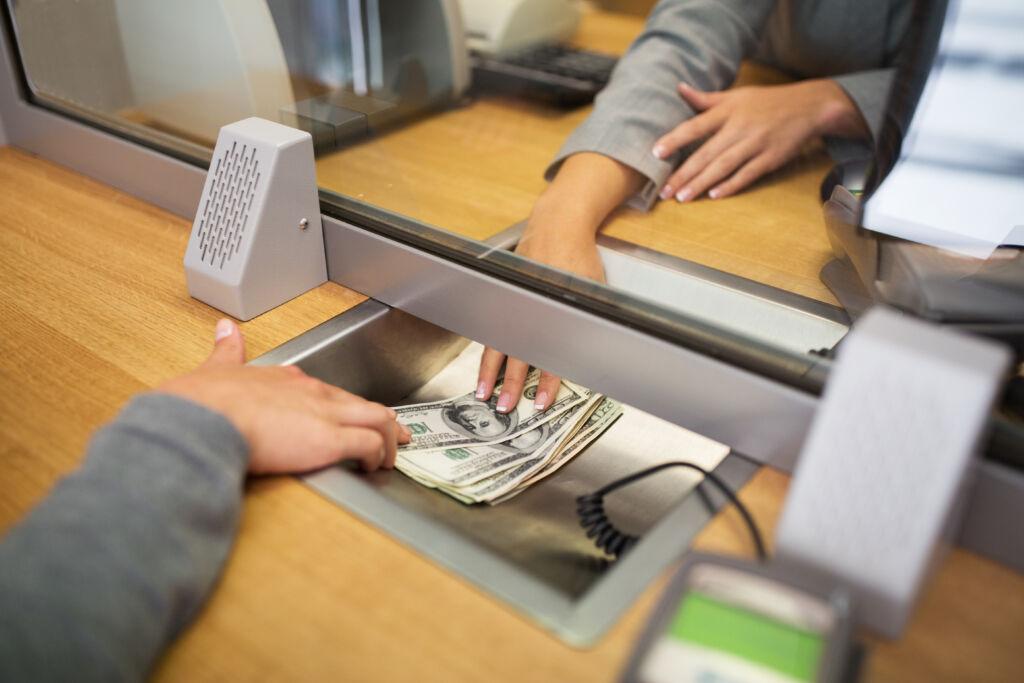 Woman Borrowing Money From Bank Teller