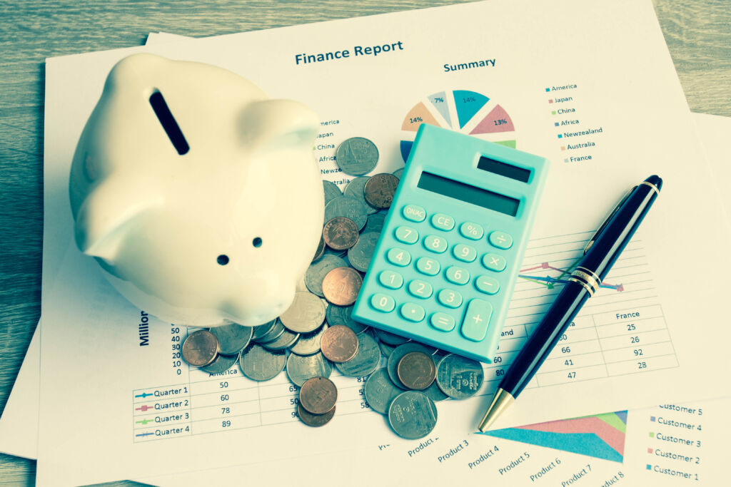 Piggy Bank and Calculator on Top of Finance Report