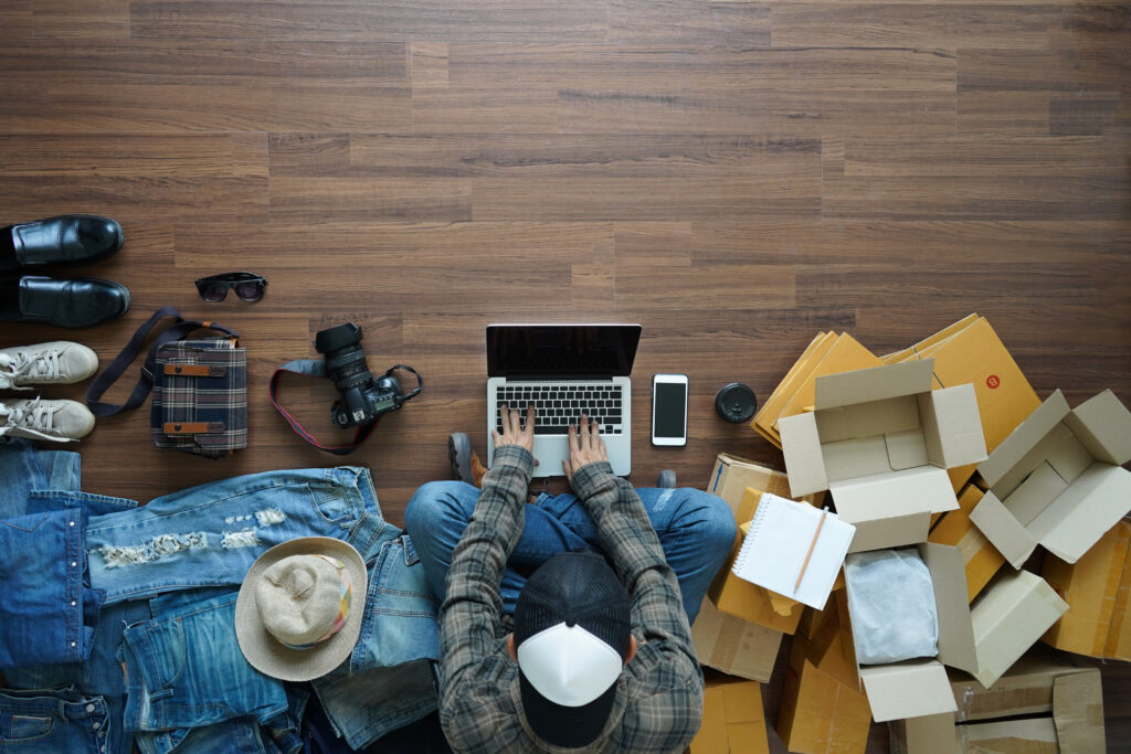 Man Shopping Online Surrounded by Open Deliveries