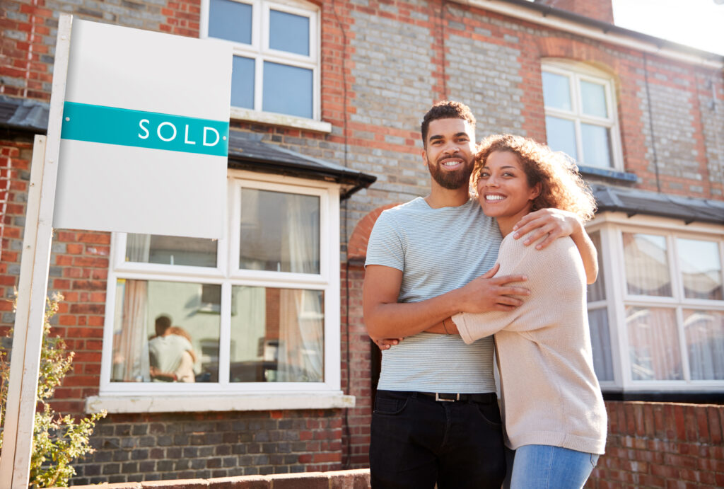 Happy Couple by Sold Real Estate Sign