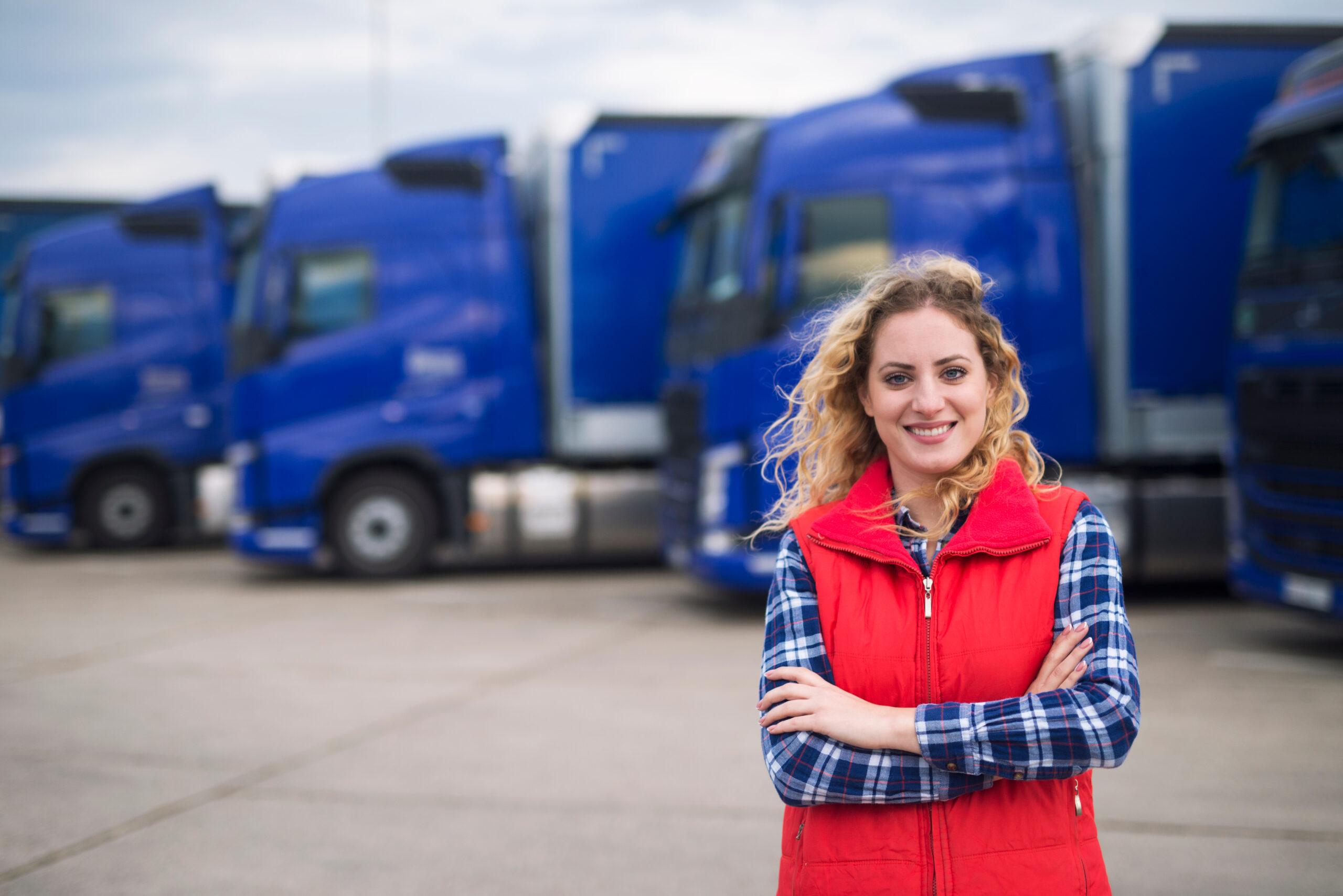 Female Trucker Smiling in Front of Trucks