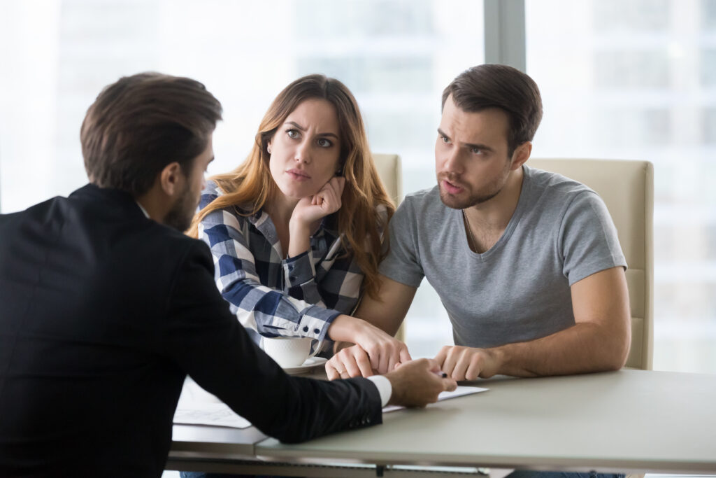 Couple Discussing Rental Scam with Business Professional