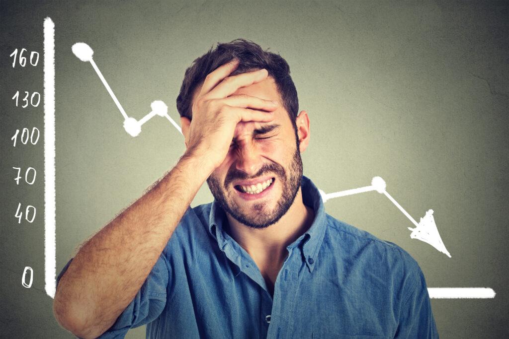 Man Upset with Financial Decline Chart Behind Him