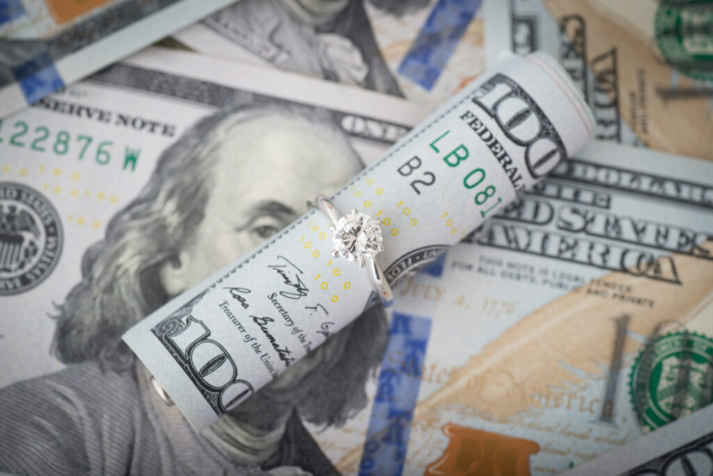 Wedding Ring Around Rolled Up $100 Dollar Bill