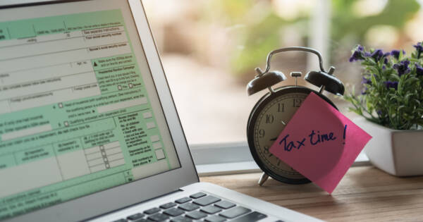 Desktop with Computer and Tax Time Note