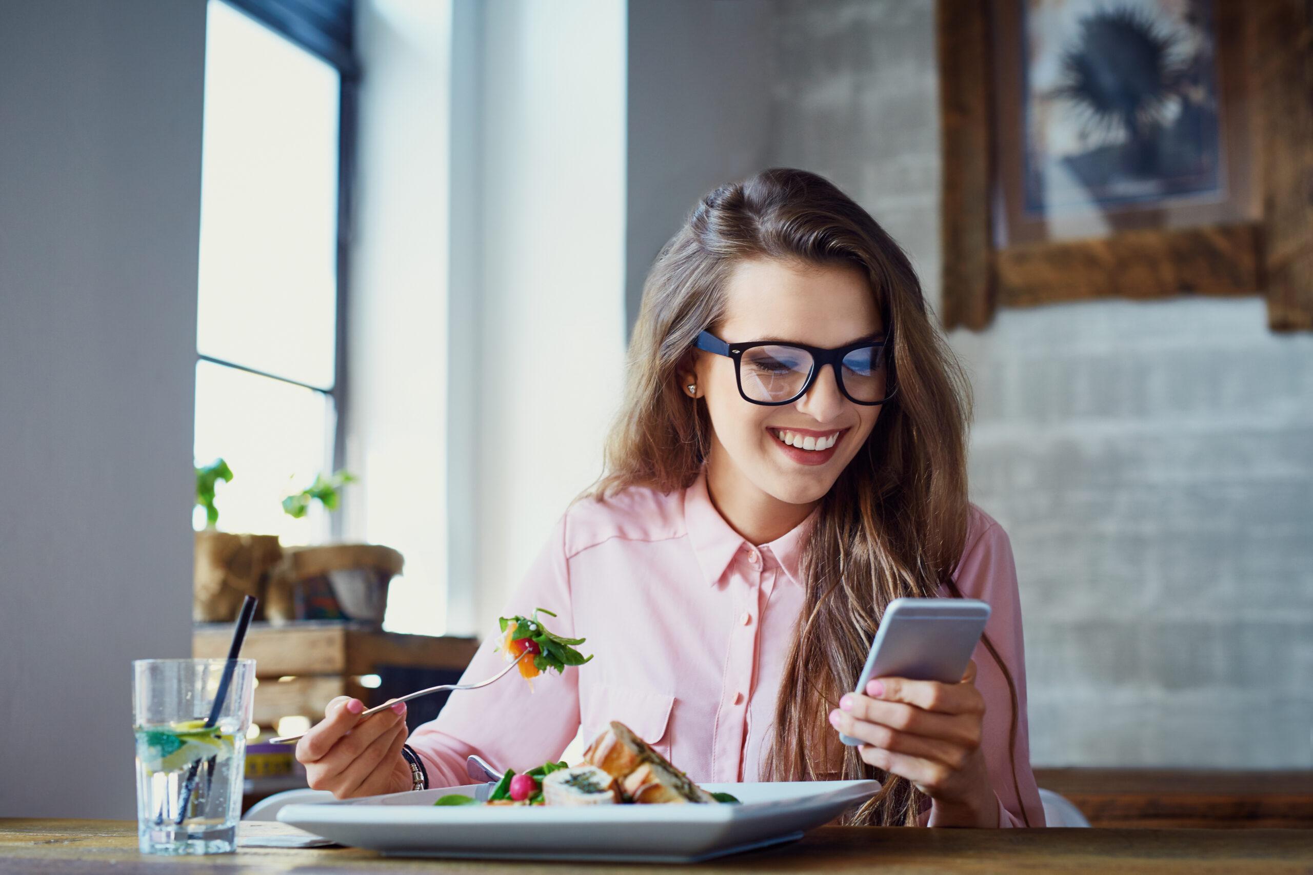 Woman eating healthy and checking her bank balance