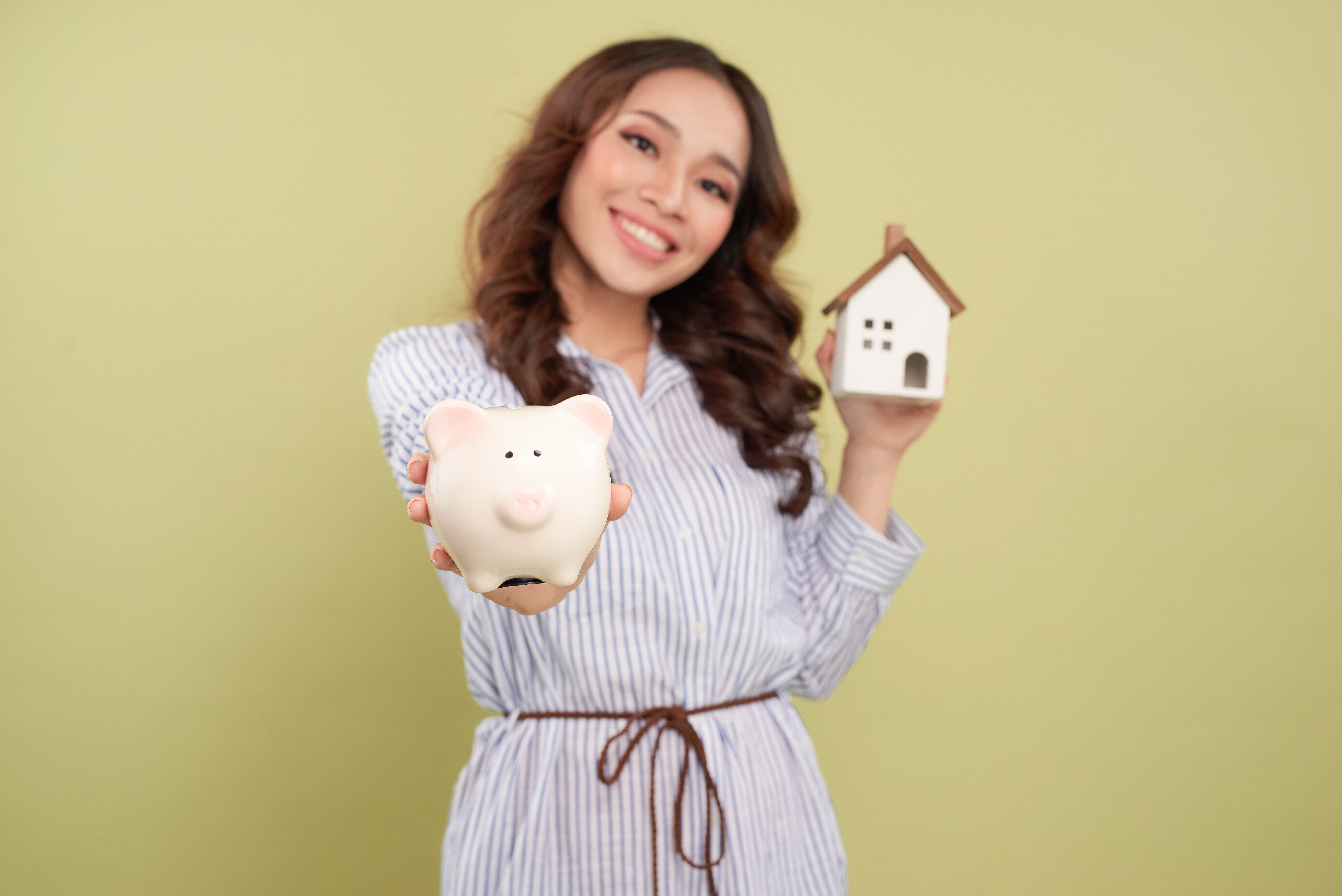 woman holding bank and house closing costs