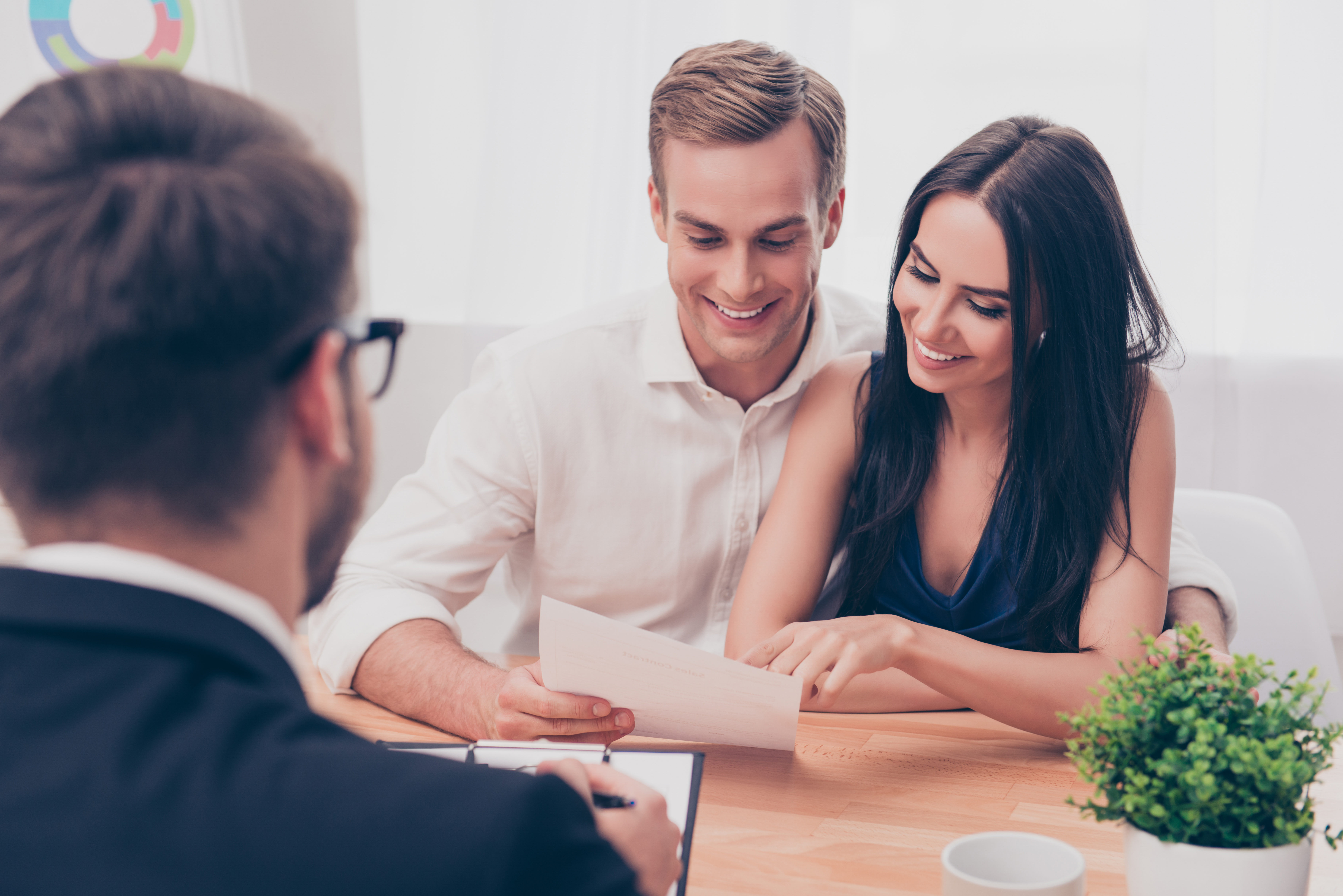 Young couple signing loan paperwork