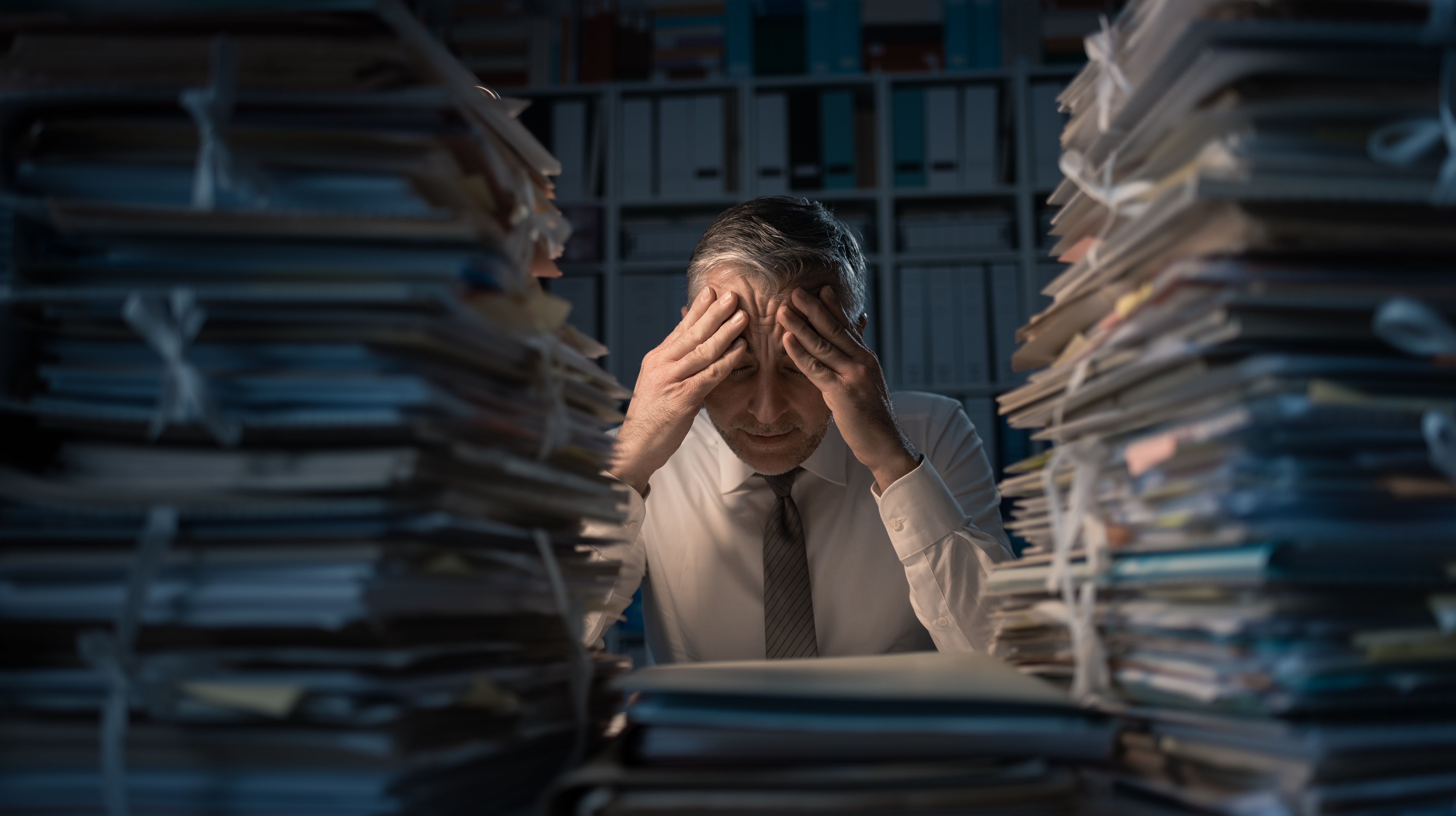 Man stressed out by mountains of work