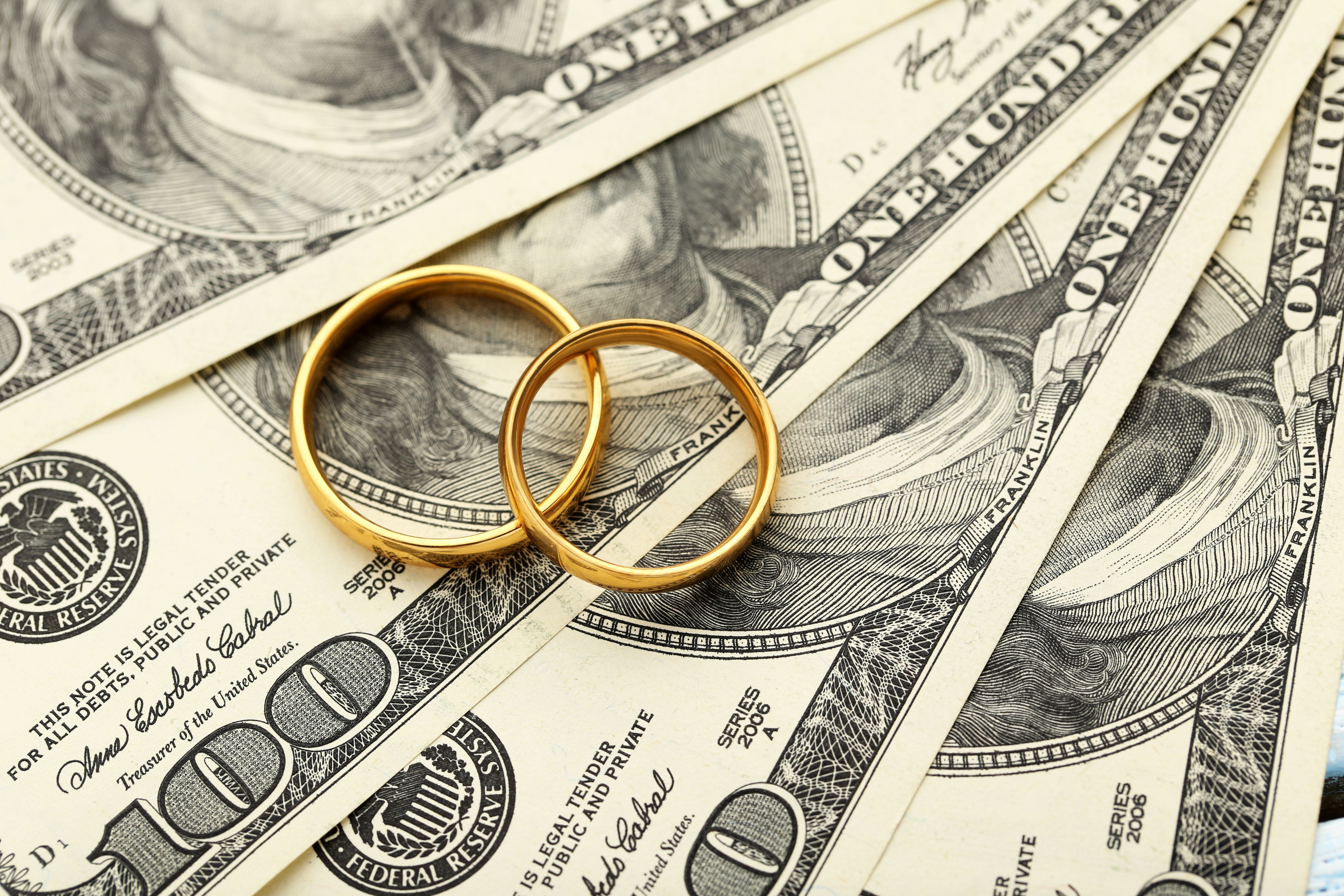 wedding rings on top of cash