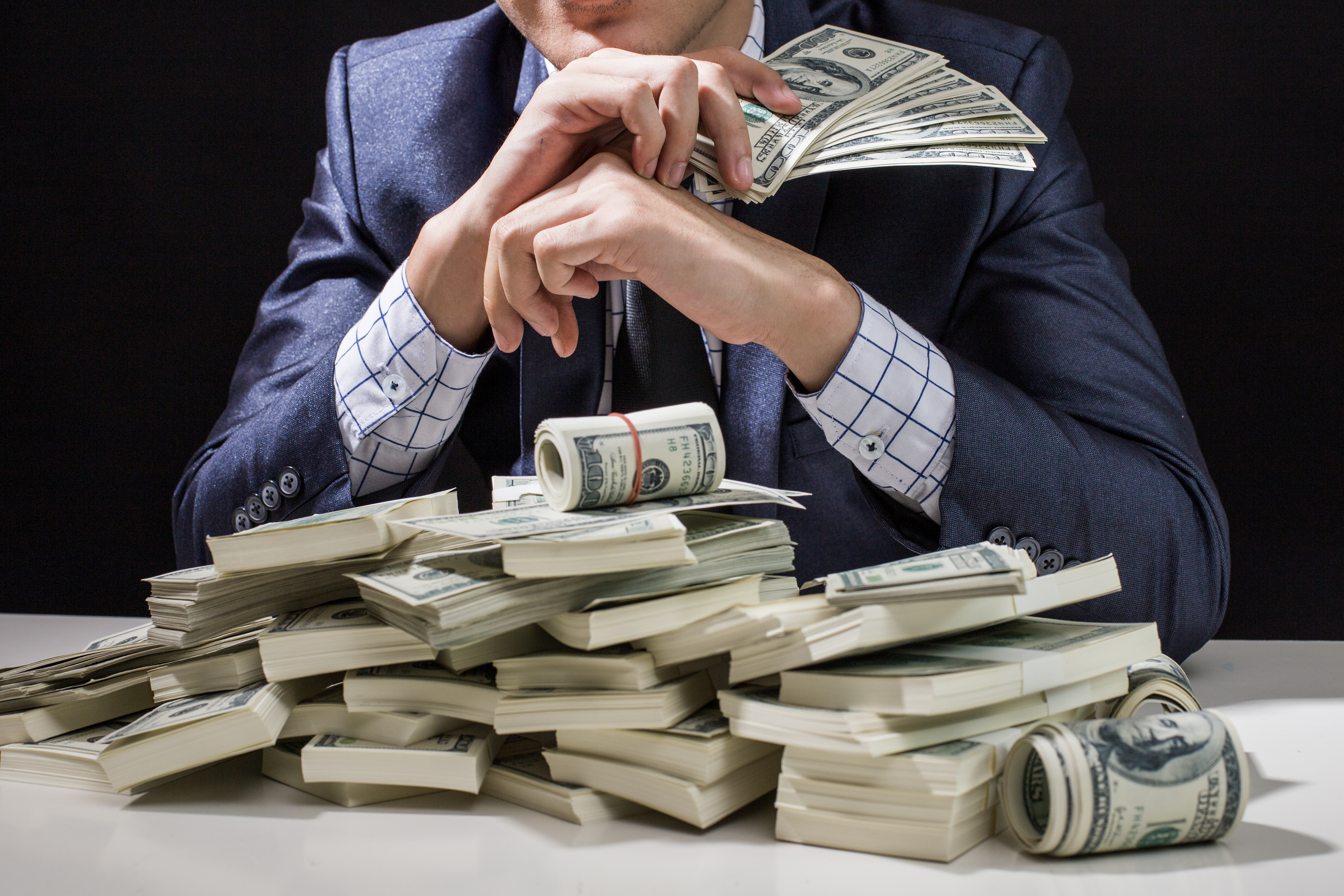 Man in suit sitting in front of pile of cash