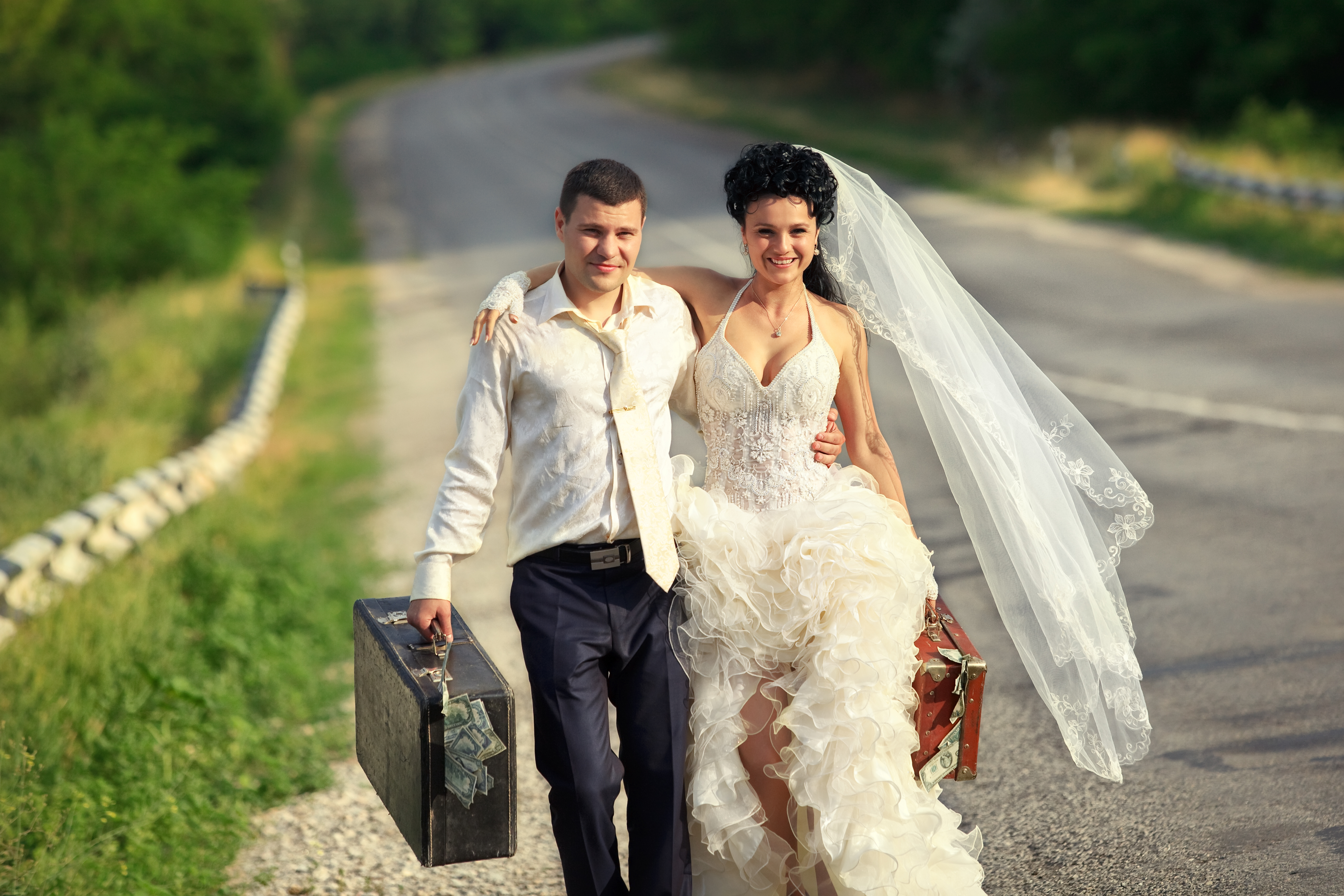 Young married couple with suitcases of cash