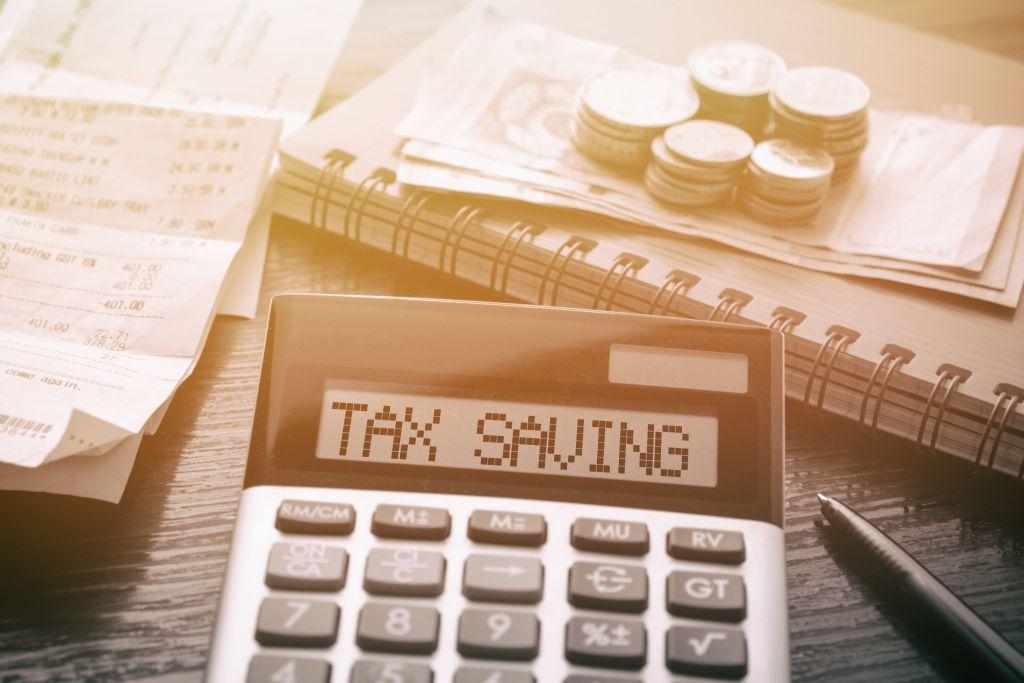 Desktop with Tax Savings on Calculator