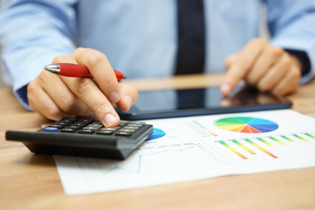 Man Crunching Numbers on Financial Charts