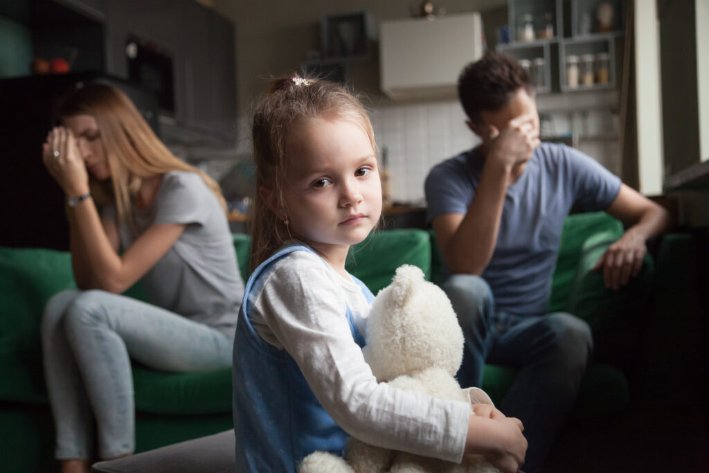 Child Sad with Parents Fighting in Background