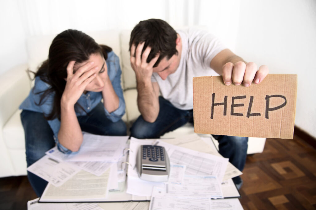 Couple Stressed About Finances Holding Help Sign
