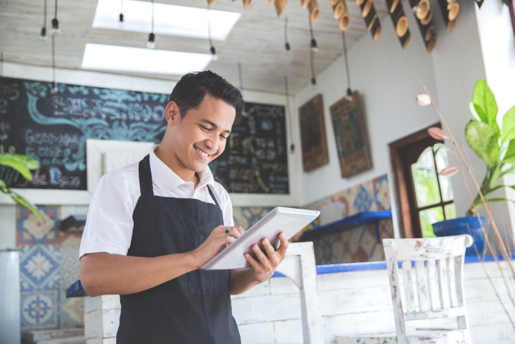 Small Business Owner Smiling at Tablet